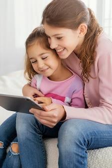 Dwie siostry razem korzystające z tabletu w domu