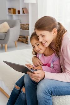Dwie siostry razem w domu za pomocą tabletu