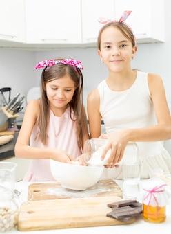 Dwie siostry robią ciasto w kuchni w dużej białej misce
