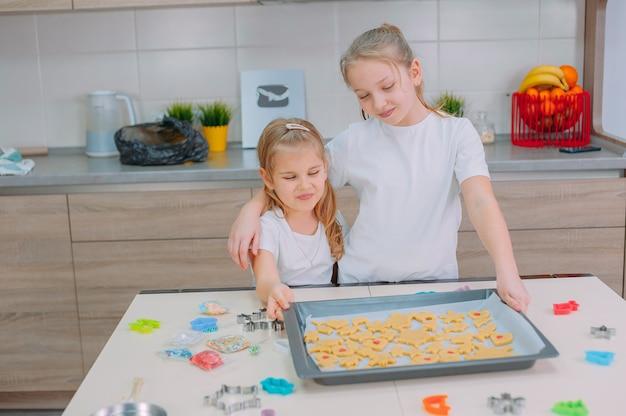 Dwie siostry robią domowe ciasteczka w kuchni.
