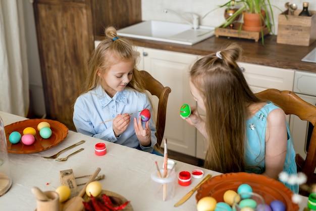 Dwie siostry są zajęte kolorowaniem pisanek w kuchni