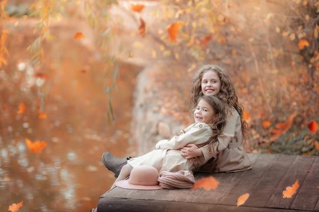 Dwie siostry siedzą jesienią na drewnianym pomoście nad brzegiem jeziora