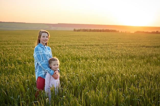 Dwie siostry siedzą na wysokiej trawie o zachodzie słońca, dziewczyny bawią się w chowanego