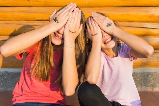 Dwie siostry siedzące na zewnątrz zakrywające oczy tatuażem oczu na dłoni