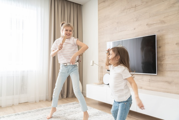 Dwie siostry świetnie się bawią, tańcząc w salonie i śpiewając karaoke