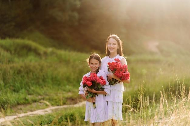 Dwie siostry ubrane w białe sukienki wspólnie bawią się latem. dziewczyny trzymają kwiaty.