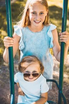 Dwie siostry w parku. starszy potrząsa młodszym na huśtawce