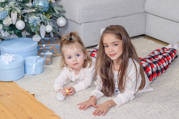 Dwie siostry w pobliżu choinki. śliczne małe dziewczynki. domowy komfort. świąteczne ozdoby.
