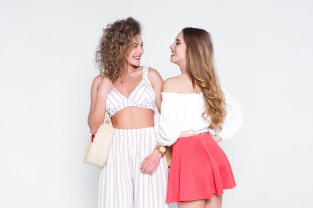 Dwie siostry w stylowym, modnym letnim kombinezonie. młoda piękna dziewczyna figlarny w pozie moda.