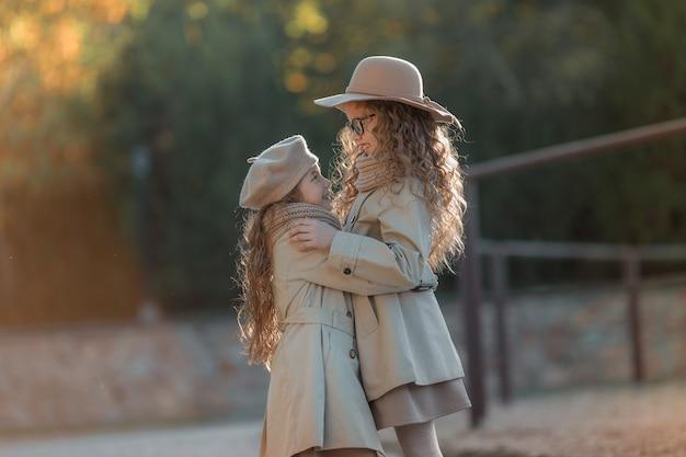 Dwie siostry w szarym jesiennym płaszczu przytulają się i patrzą na siebie