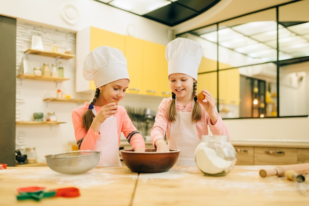 Dwie siostrzyczki gotują w czapkach, przygotowywanie ciastek na kuchni. dzieci gotują ciasto, dzieciaki robią ciasto, dzieci przygotowują ciasto