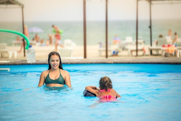 Dwie siostrzyczki pływają w moim dużym basenie z czystą, błękitną wodą w pobliżu hotelu