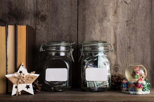 Dwie skarbonki z różnymi kwotami pieniędzy i miejscem na tekst