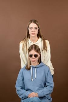 Dwie śliczne blond nastolatka w bluzach i okularach