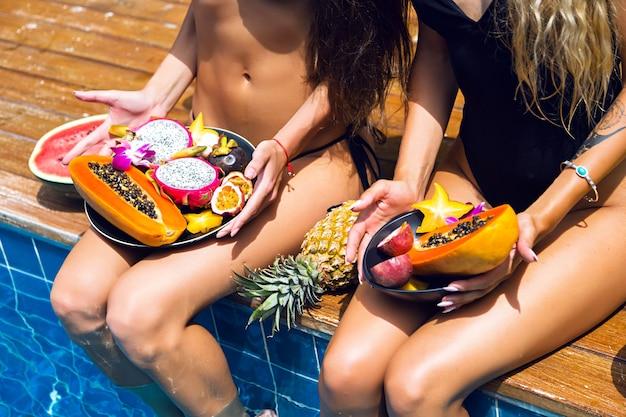 Dwie śliczne blondynki i brunetki bawią się i szaleją na imprezie z owocami tropikalnymi, seksowne czarne bikini, dużo słodkiego wegańskiego jedzenia, egzotyczne wakacje, pozowanie przy basenie, letni wizerunek mody.
