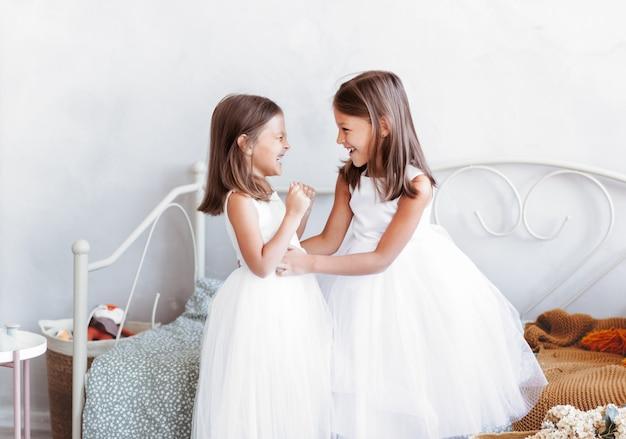 Dwie śliczne dziewczynki bawią się w jasnym pokoju. zabawne, kochane dzieci dobrze się bawią