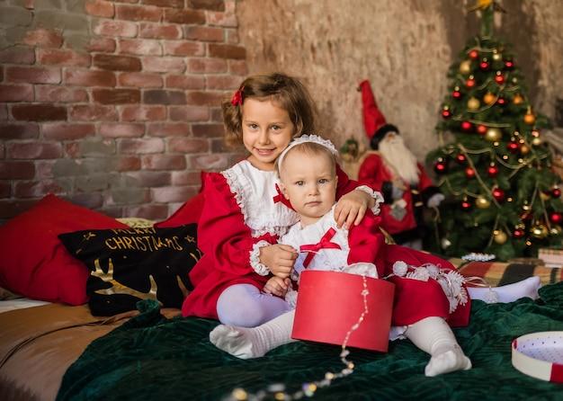 Dwie śliczne dziewczynki w czerwonych świątecznych sukienkach siedzą na łóżku z prezentami choinki