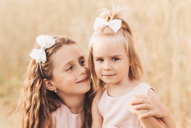 Dwie śliczne dziewczynki w sukienkach przytulających się w naturze latem