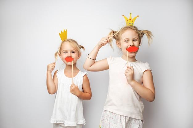 Dwie śliczne dziewczynki z papierową koroną i czerwonymi ustami pozują białe tło w domu