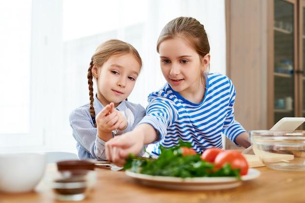 Dwie śliczne dziewczyny gotujące w domu