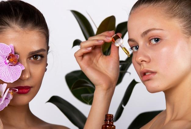 Dwie śliczne dziewczyny pozujące z serum na ścianie dużego kwiatu. pojęcie pielęgnacji skóry, regeneracji, regeneracji, spa. wysokiej jakości zdjęcie