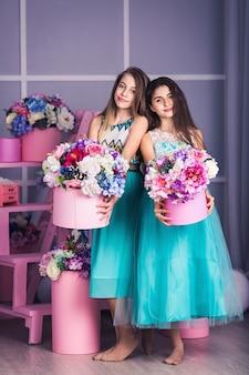 Dwie śliczne dziewczyny w niebieskich sukienkach z dekoracją kwiatów w koszyczkach