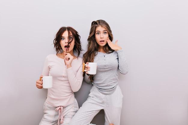 Dwie śliczne dziewczyny w piżamie wygłupiające się na szarej ścianie. dobrze się bawią.