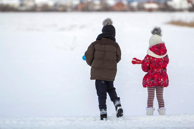 Dwie śliczne małe dzieci w ciepłych ubraniach z jasnymi klipami śniegu, grając, bawiąc się, robiąc śnieżki w zimowy zimny dzień na białym jasnym tle niewyraźne kopii. aktywność na świeżym powietrzu, zabawy wakacyjne.