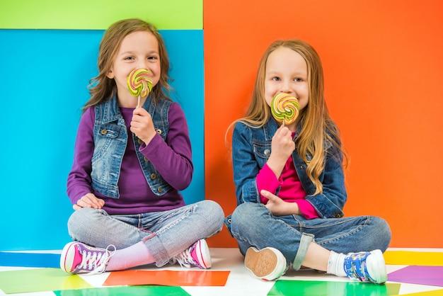 Dwie śliczne małe dziewczynki siedzą na podłodze.
