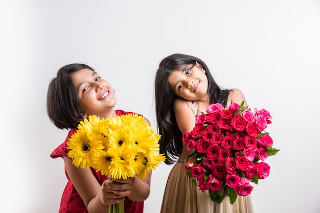 Dwie śliczne małe indyjskie dziewczyny trzymające bukiet lub bukiet świeżych czerwonych róż lub kwiatów gulab. pojedynczo na białym tle