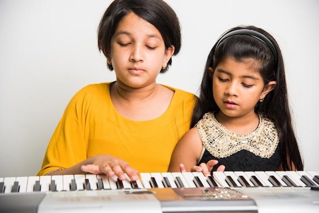 Dwie śliczne małe indyjskie lub azjatyckie dziewczyny grające na pianinie lub klawiaturze, instrumencie muzycznym, na białym tle