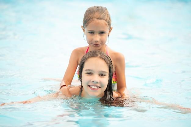 Dwie śliczne małe siostry dziewczyny pływają w basenie podczas wakacji w słoneczny, ciepły letni dzień. koncepcja długo oczekiwanego urlopu.