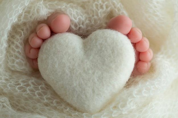 Dwie śliczne malutkie nóżki dziecka owinięte w biały kocyk z dzianiny. i dzianinowe serce z wełnianych nici. zdjęcie wysokiej jakości