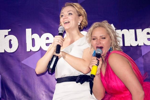 Dwie śliczne młode kobiety w odświętnych sukniach śpiewają karaoke w barze rosja, jarosław, 22.02.2019