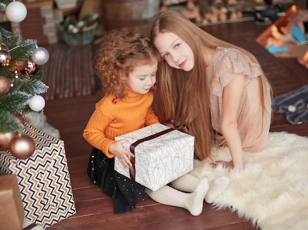 Dwie śliczne siostry siedzą na podłodze w wigilię bożego narodzenia.