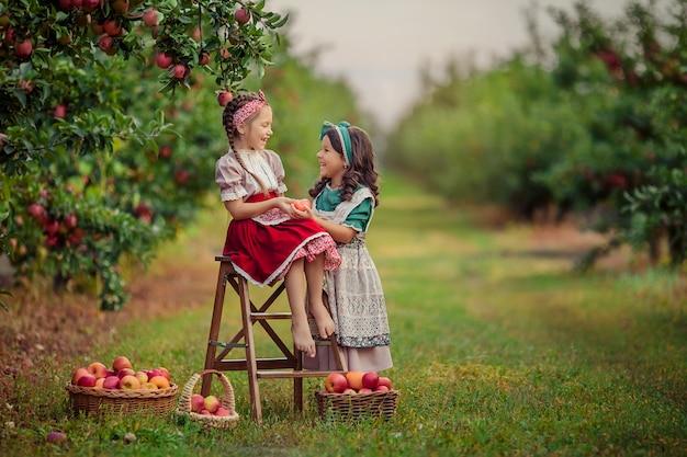 Dwie śliczne siostry w stylu vintage w sadzie jabłkowym śmieją się i baw się dobrze