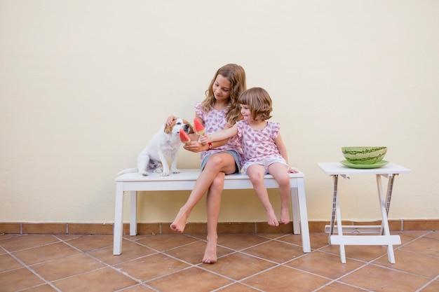 Dwie śliczne siostrzane dzieci jedzące lody z arbuza ze swoim uroczym psem. rodzinna miłość i styl życia na zewnątrz