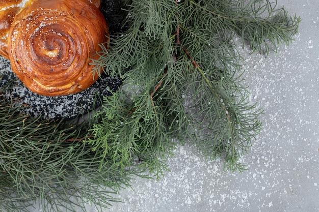 Dwie słodkie bułeczki na małej desce obok sosnowych gałęzi na marmurowym stole.
