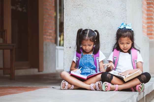 Dwie słodkie dziewczyny azjatyckich uczniów czytając książkę razem w szkole z zabawy i szczęścia