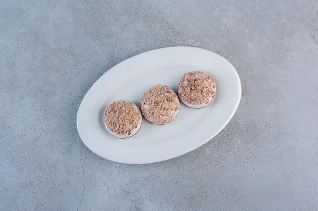 Dwie smaczne kulki trufli umieszczone na białym talerzu.