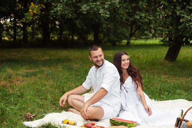 Dwie śmiejące się para w białych ubraniach, uśmiechając się, siedząc na kocu z owocami w letnim parku otoczonym drzewami.
