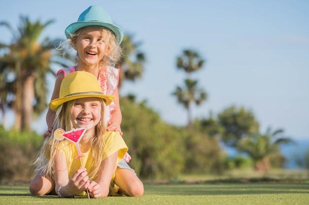 Dwie śmieszne dziewczynki z maską papieru. urodziny dla dzieci, zabawa w okresie letnim.