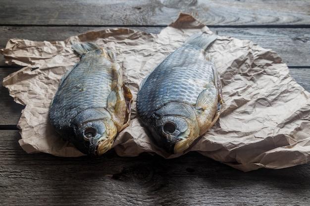 Dwie solone suche ryby vobla na zmiętym papierze rzemieślniczym na drewnianej, pysznej przekąsce do piwa