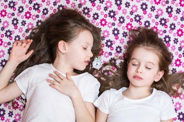Dwie śpiące dziewczynki i biały budzik pomiędzy nimi. widok z góry
