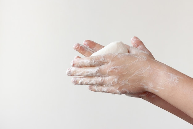 Dwie spienione ręce trzymają mydło w dłoniach