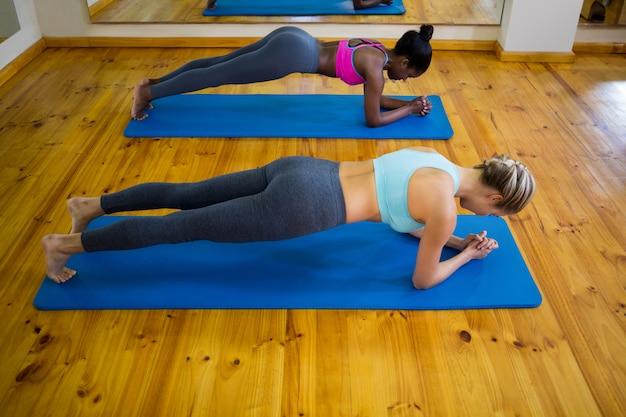 Dwie sprawne kobiety robią ćwiczenia rozciągające na macie