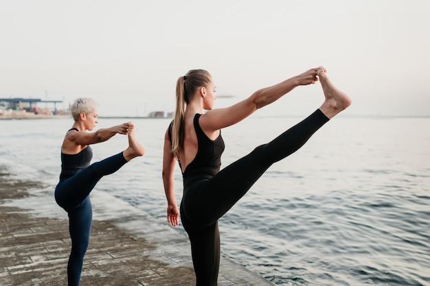 Dwie sprawne, sportowe kobiety rozciągają nogi w synchronizacji na plaży