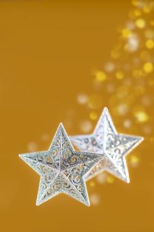 Dwie srebrne gwiazdy bożonarodzeniowe na złotym tle rozmytych świateł
