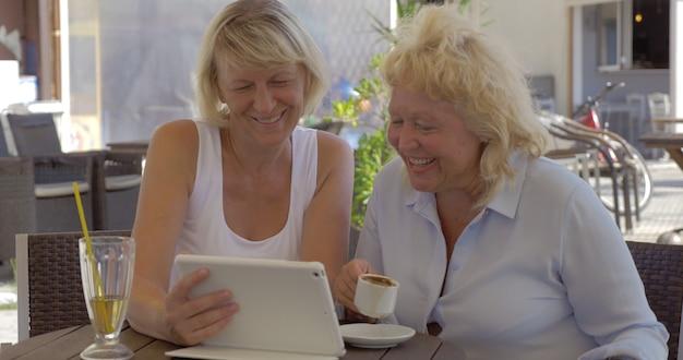Dwie starsze kobiety oglądają zdjęcia na podkładce w ulicznej kawiarni