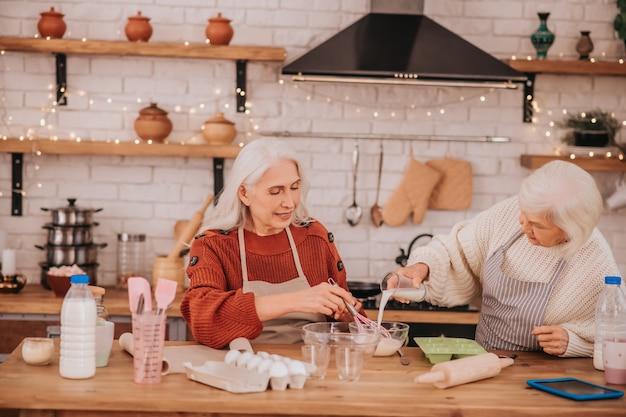 Dwie starsze kobiety wyglądające na zajęte w kuchni